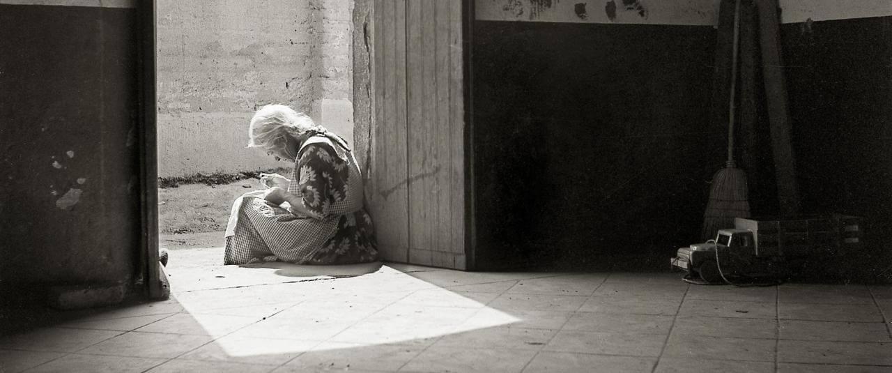 Anciana sentada en el umbral de la casa de un pueblo | El fotógrafo Juan Rulfo | Museo Amparo, Puebla